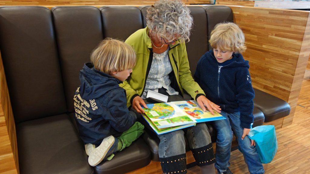 A grandparent reads to her grand children