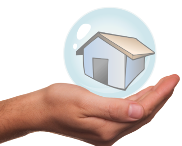 A hand cradling a house - home insurance concept