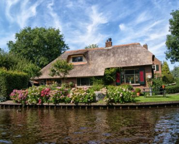 A pretty thatched cottage by a river