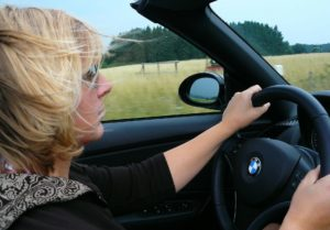 A woman driving a convertible car