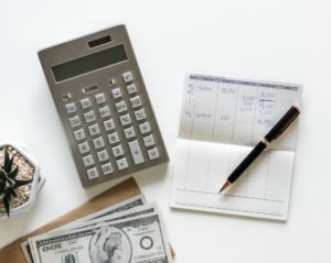 Keeping track of finances with a calculator and a notebook