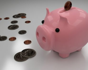 Dropping money into a piggy bank