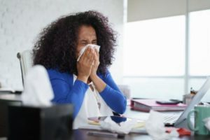 An employee sneezing in an office