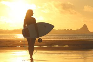 A woman surfer on a sunny beach