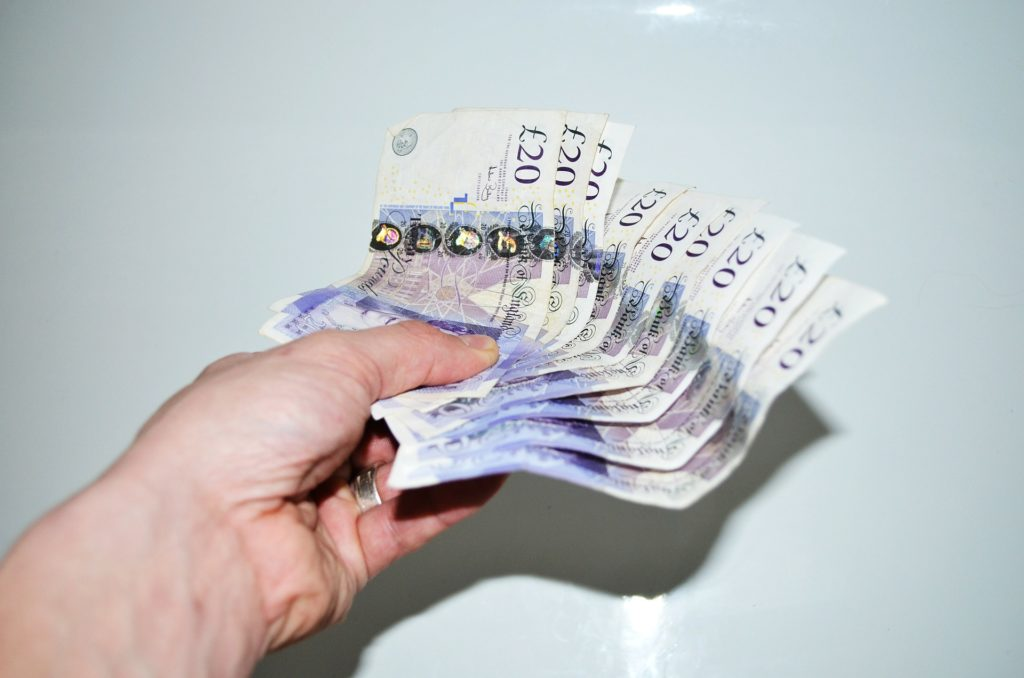 A hand holding £20 notes