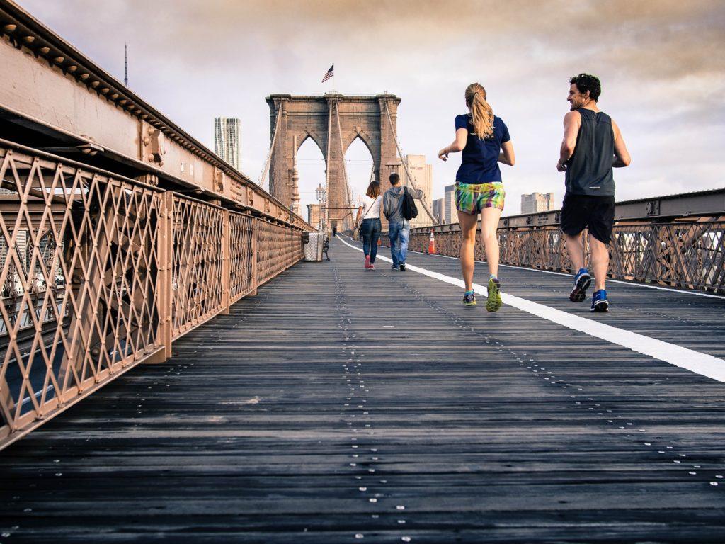 A couple running along a bridge