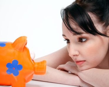Young woman looking at her piggy bank