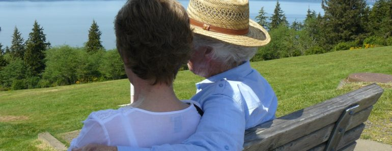 A happy elderly couple relaxing by a lake