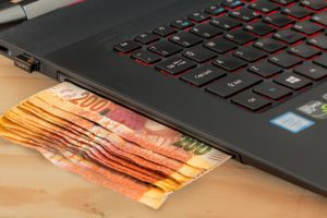 A laptop and money