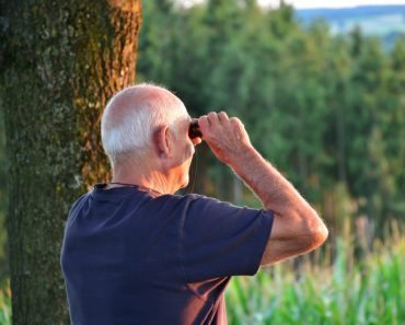 A male pensioner looking through binoculars