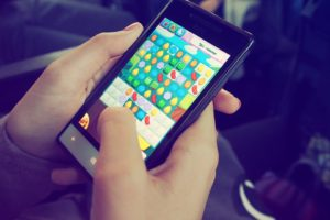 Playing Candy Crush on a mobile phone