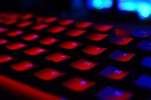 A gaming keyboard lit with red lights