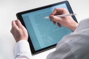 A writing on a tablet with a pen