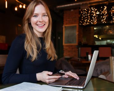 A smiling business woman using a laptop