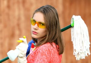 A young woman cleaning with a mop
