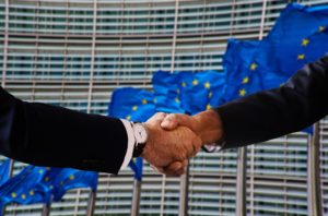 Shaking hands in front of the European flag