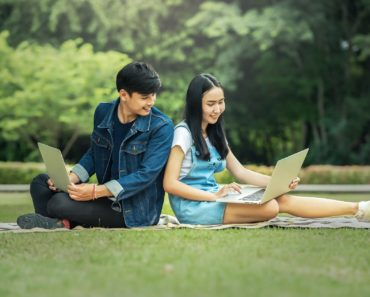 A happy couple using their laptops in the park