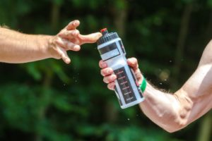 A sports water bottle passed between two people