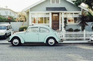A VW Beetle parked outside a house