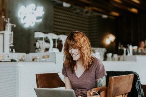 A happy woman using a laptop in a cafe