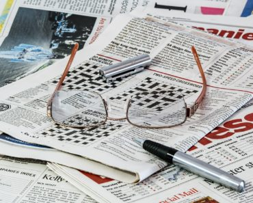 Newspapers a pen and glasses