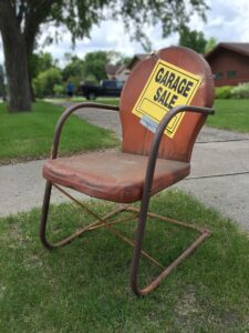 A garage sale sign on an old chair