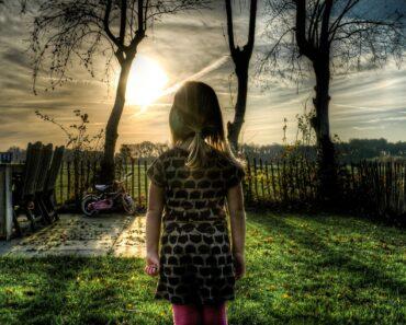 A girl standing in a sunny garden