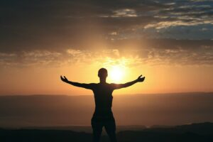 A happy woman embracing the sunrise
