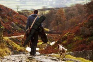 A hunter walking with his gun dog