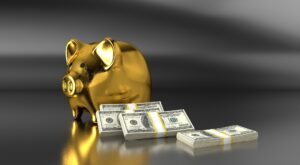 A golden piggy bank and stacks of dollar bills