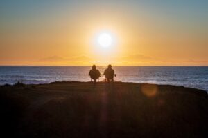 A couple sitting on a beach at sunset
