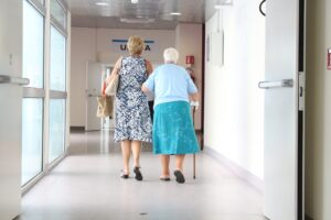 An elderly lady being help to walk along a corridor