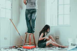 A couple painting and decorating a room