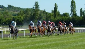 Horses galloping down a race course