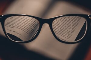 A pair of reading glasses and a book