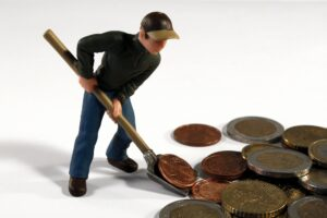 A toy man shovelling money