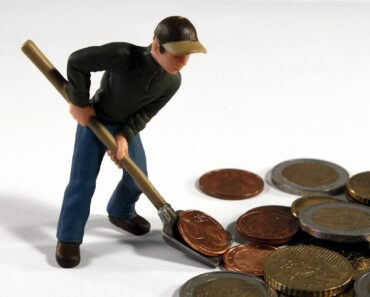 A toy man shovelling money