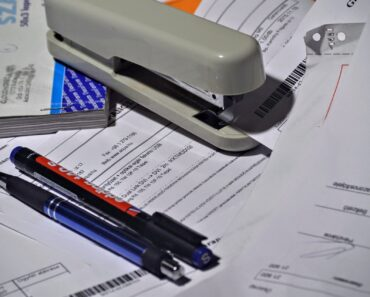 A stapler and paperwork on a crowded desk