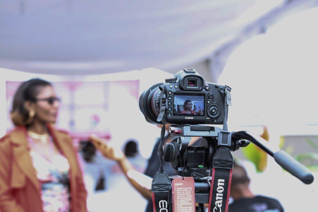 A video camera filming a vlogger