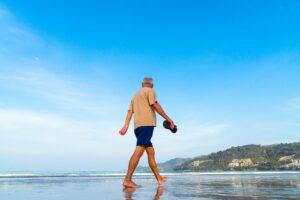 A retired man walking along a beach