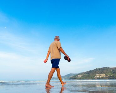 A retired man walking along a beach