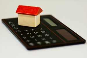 A  mortgage concept with a toy house and a calculator