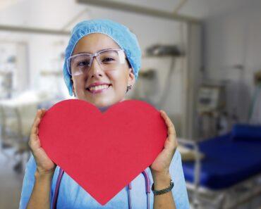 A caring nurse holding a cardboard heart