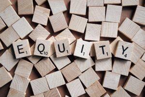 Equity written in wooden scrabble pieces