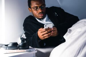 A man using a phone in bed