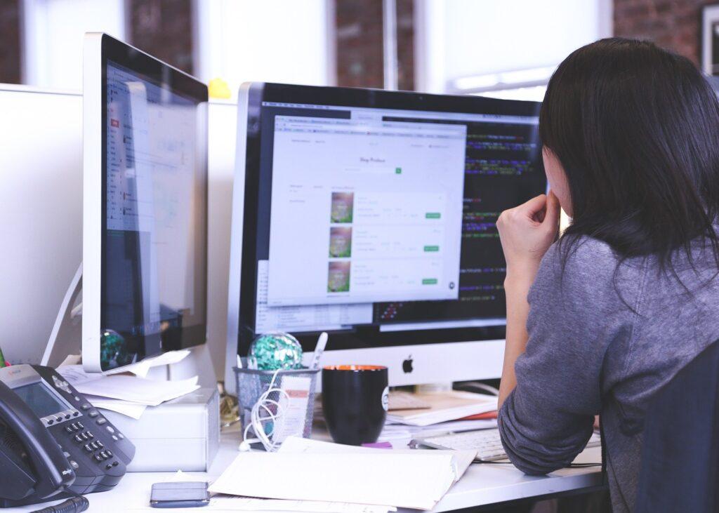 Using a desktop computer at an untidy desk