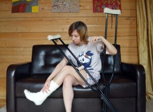 Young woman holding a pair of crutches