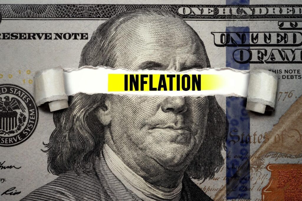Inflation tearing a hole in a 100 dollar note