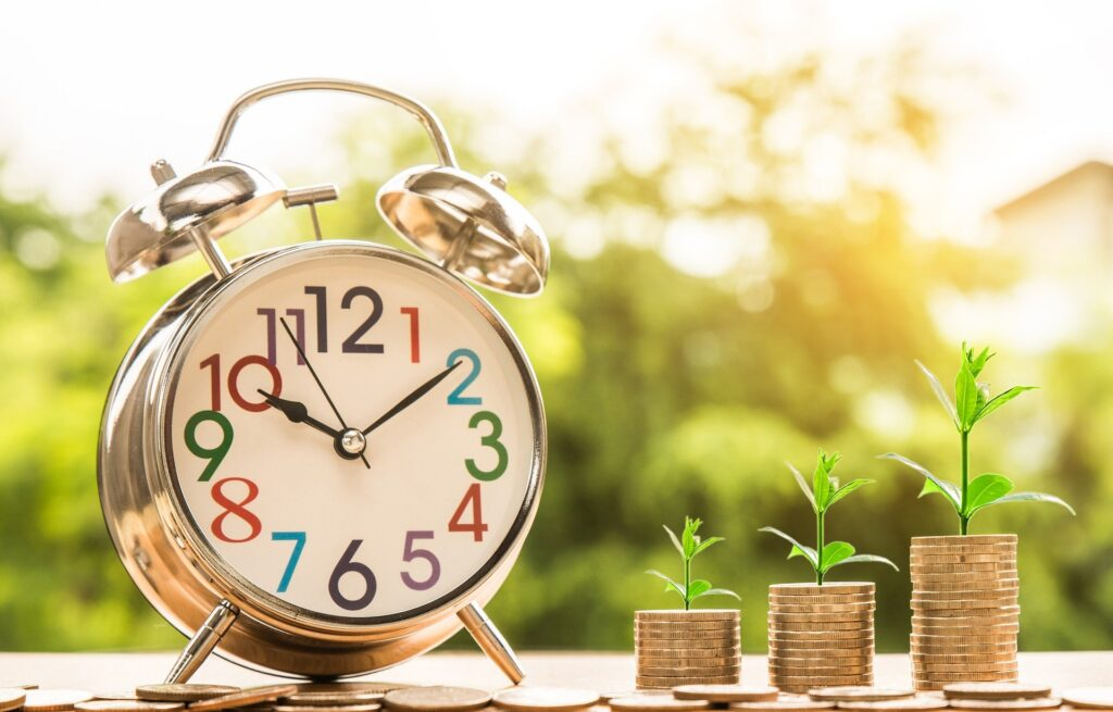 An alarm clock and growing columns of money