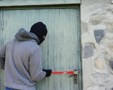 A thief breaking in with a crowbar